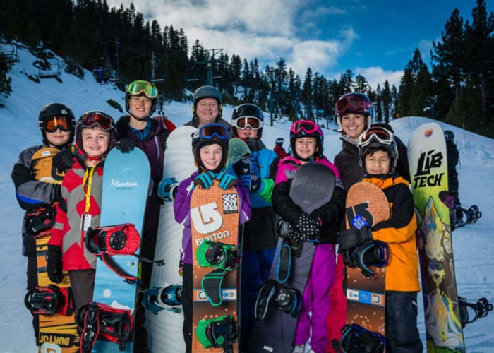 SOS Outreach youth posing with their snowboards during a trip