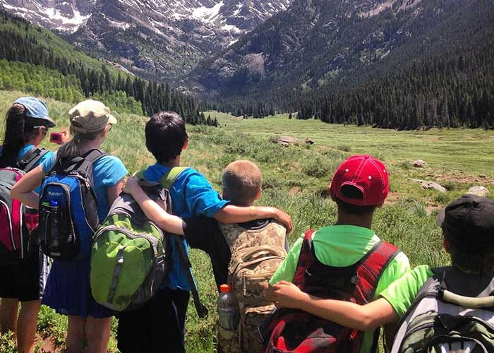 SOS Outreach youth on a hike through beautiful mountains