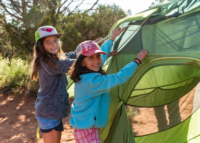 Girls putting up tent